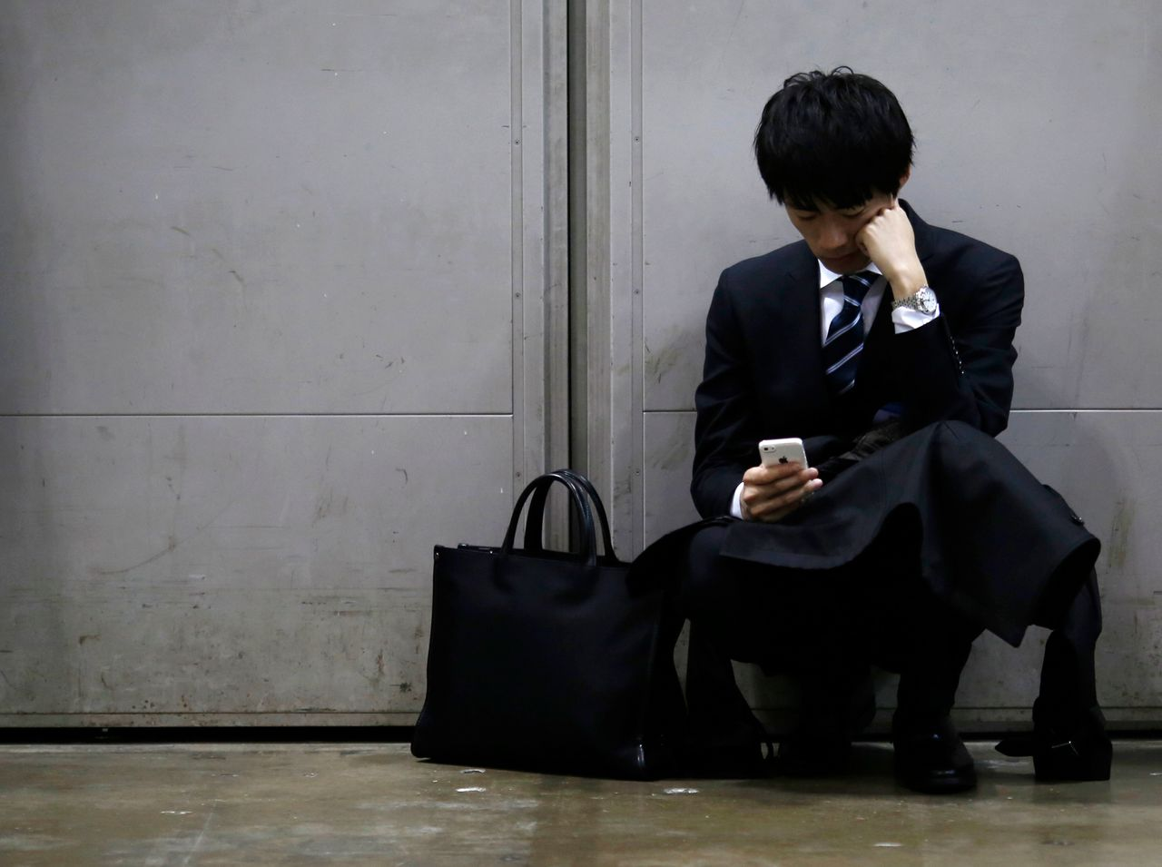 A job seeker looks at his cellphone during a job fair for graduates in Tokyo, 2015. Permanent jobs are harder to come by in Japan. Since the financial crisis in 2008, much of employment growth has been in fixed-term, part-time or temporary work.