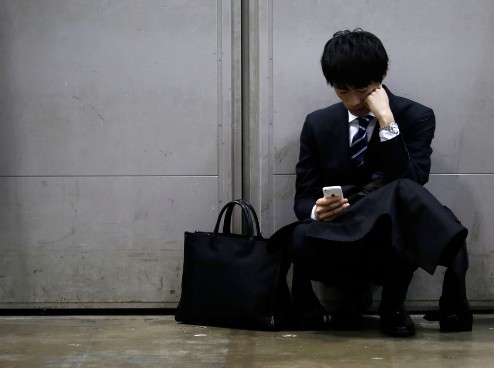 A job seeker looks at his cellphone during a job fair for graduates in Tokyo, 2015. Permanent jobs are harder to come by
