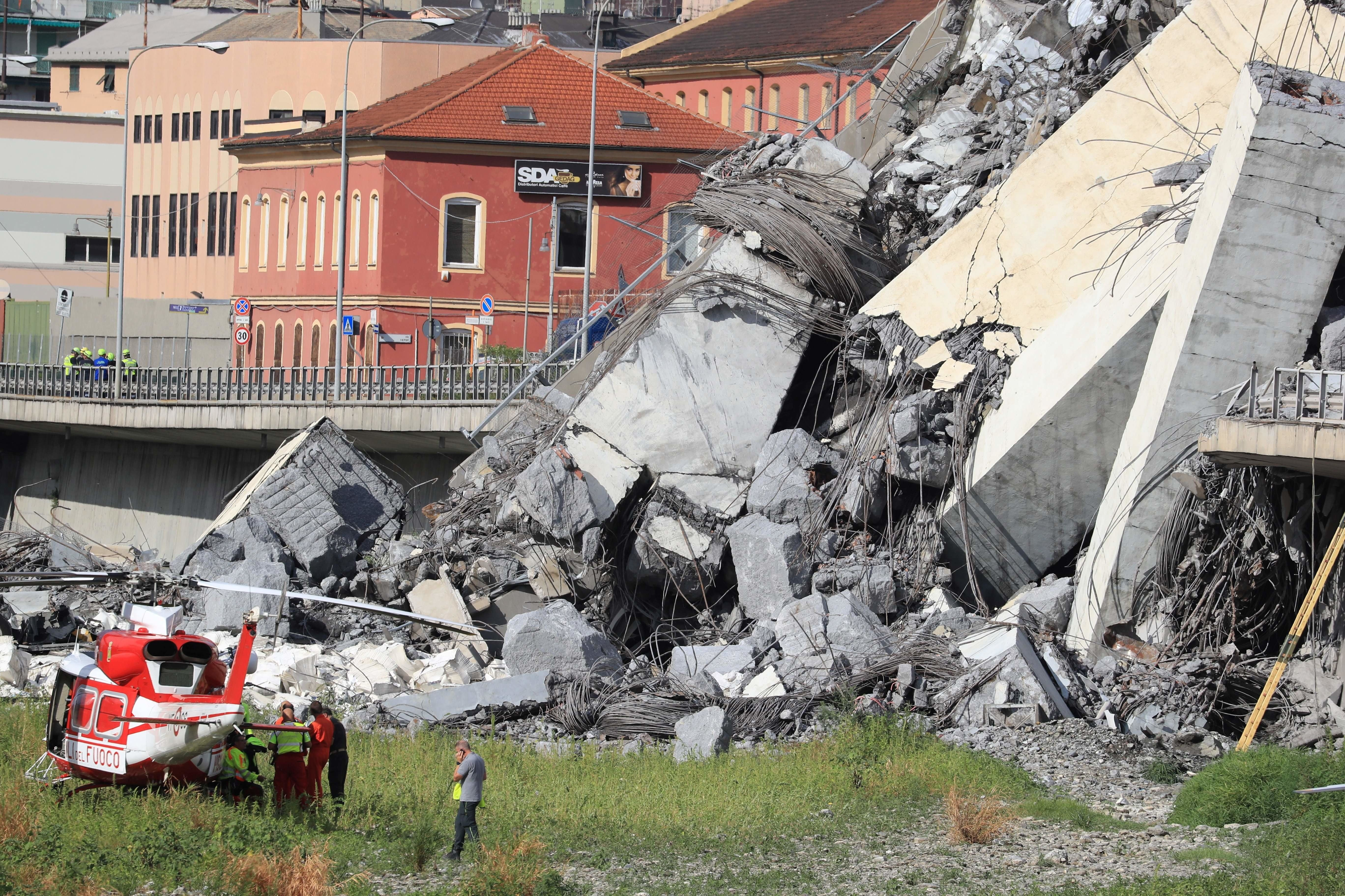 Rescuers work at the site where the Morandi motorway bridge collapsed in Genoa on August 14, 2018. - At least 30 people were killed on August 14 when the giant motorway bridge collapsed in Genoa in northwestern Italy. The collapse of the viaduct, which saw a vast stretch of the A10 freeway tumble on to railway lines in the northern port city, was the deadliest bridge failure in Italy for years, and the country's deputy transport minister warned the death toll could climb further. (Photo by Valery HACHE / AFP)        (Photo credit should read VALERY HACHE/AFP/Getty Images)