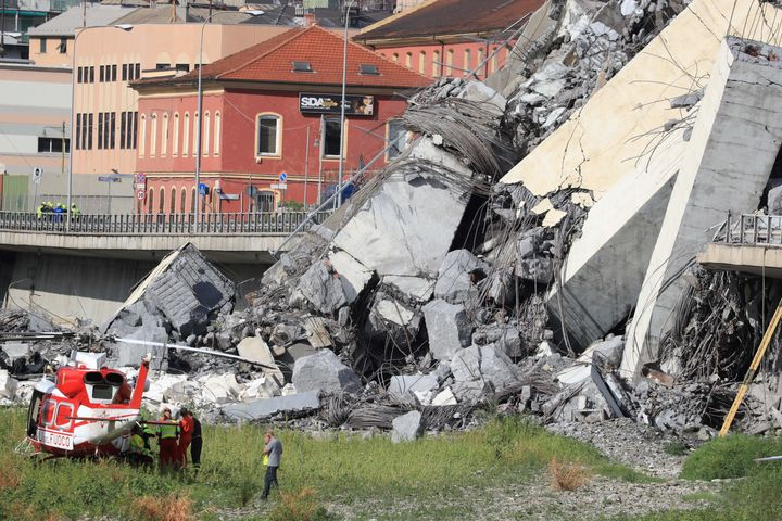 Rescuers work at the site where the Morandi motorway bridge collapsed in Genoa on August 14, 2018.