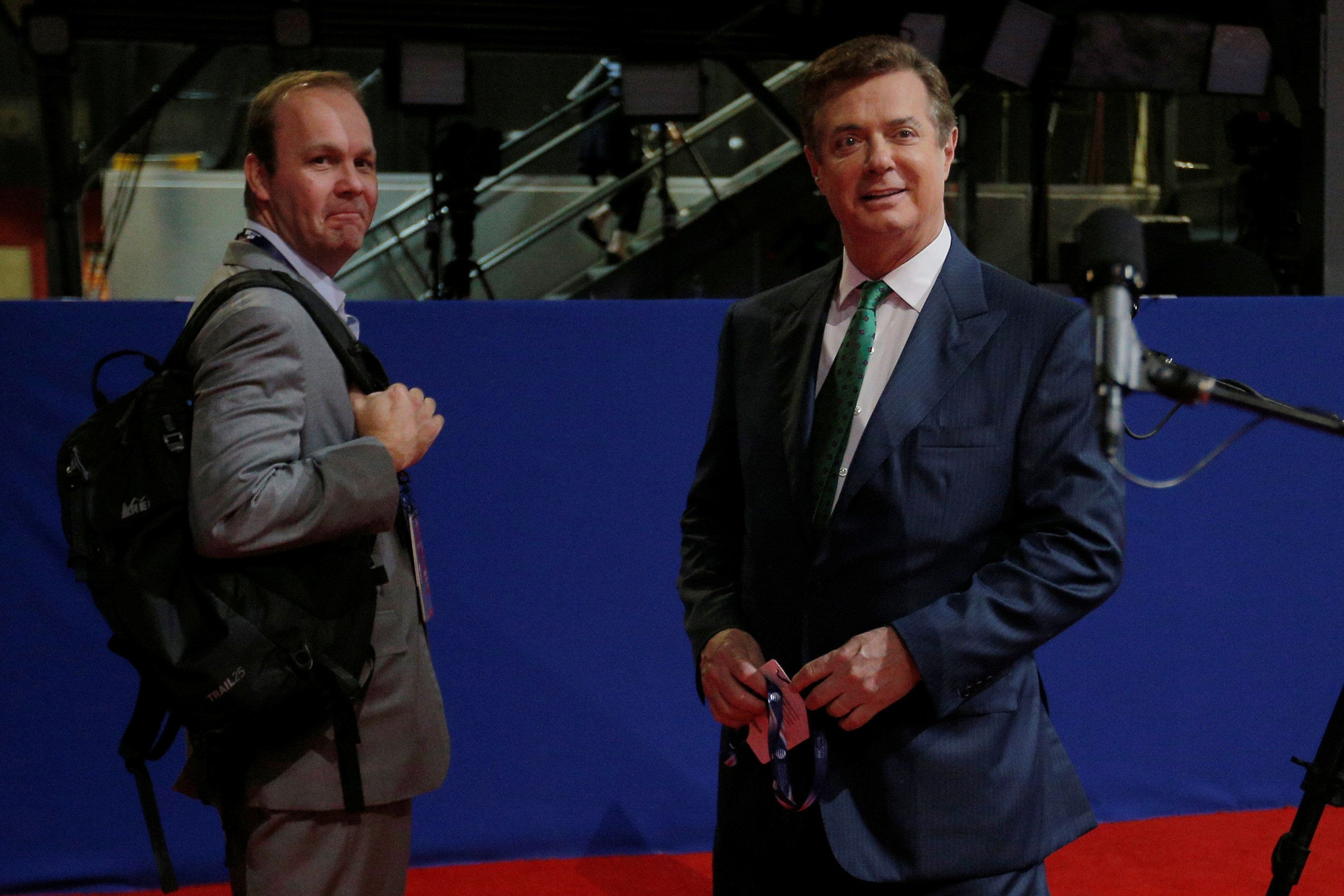 Paul Manafort (R), campaign manager to Republican Presidential Candidate Donald Trump, and his assistant Rick Gates stand on the floor of the Republican National Convention in Cleveland, Ohio, U.S. July 17, 2016.   Picture taken July 17, 2016.  REUTERS/Brian Snyder