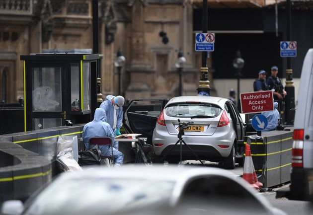 Forensic officers by the car that crashed into security barriers outside the Houses of Parliament, Westminster,
