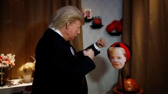 A performer with a mask of U.S. President Donald Trump hits a punching ball with a mask of German Chancellor Angela Merkel in the Madame Tussauds wax museum in Berlin, Germany, August 14, 2018. REUTERS/Hannibal Hanschke