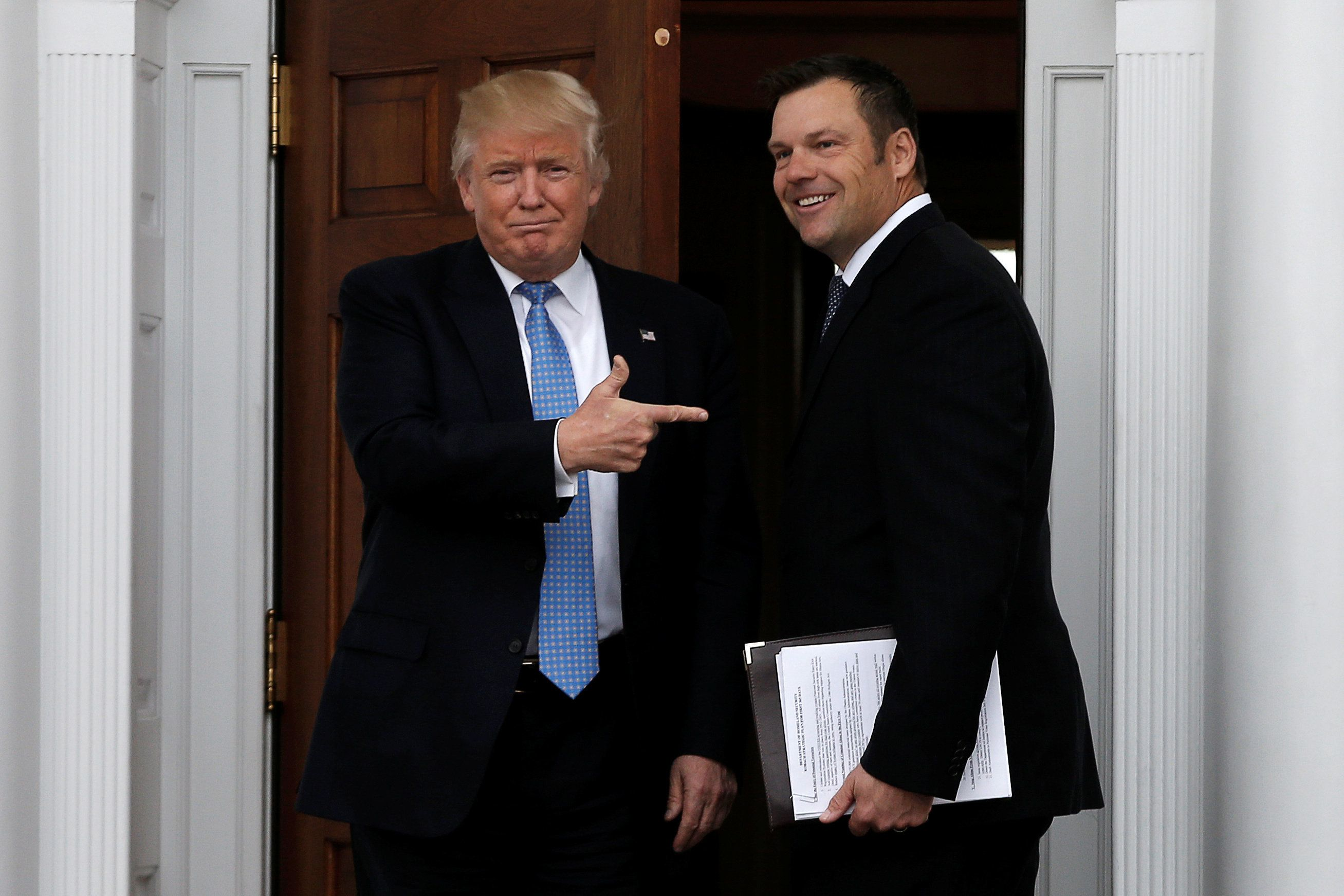 U.S. President-elect Donald Trump stands with Kansas Secretary of State Kris Kobach before their meeting at Trump National Golf Club in Bedminster, New Jersey, U.S., November 20, 2016.  REUTERS/Mike Segar
