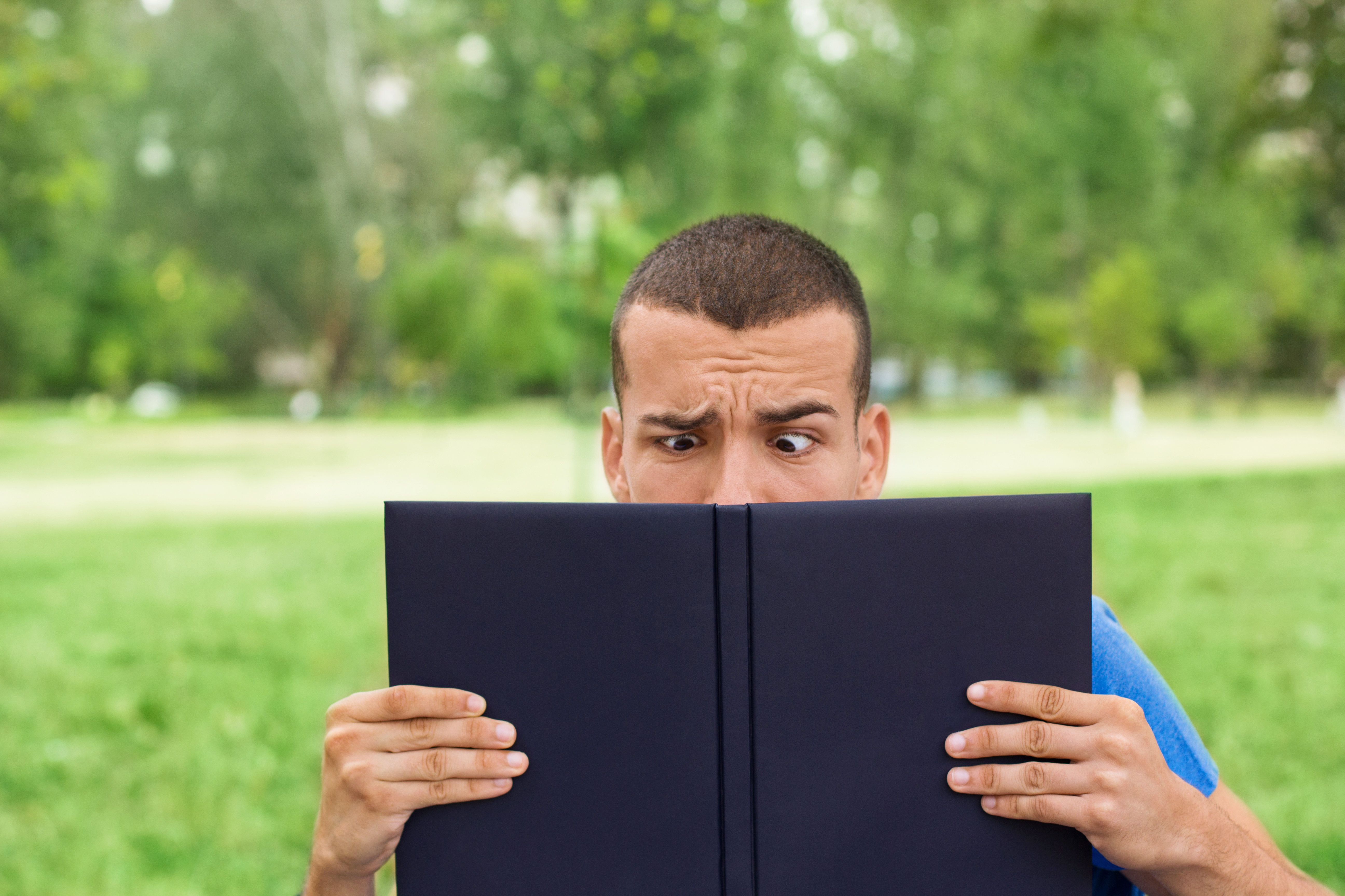 'Close-up portrait of male frowned student peeking over the book, eyes behing a book, copy space'