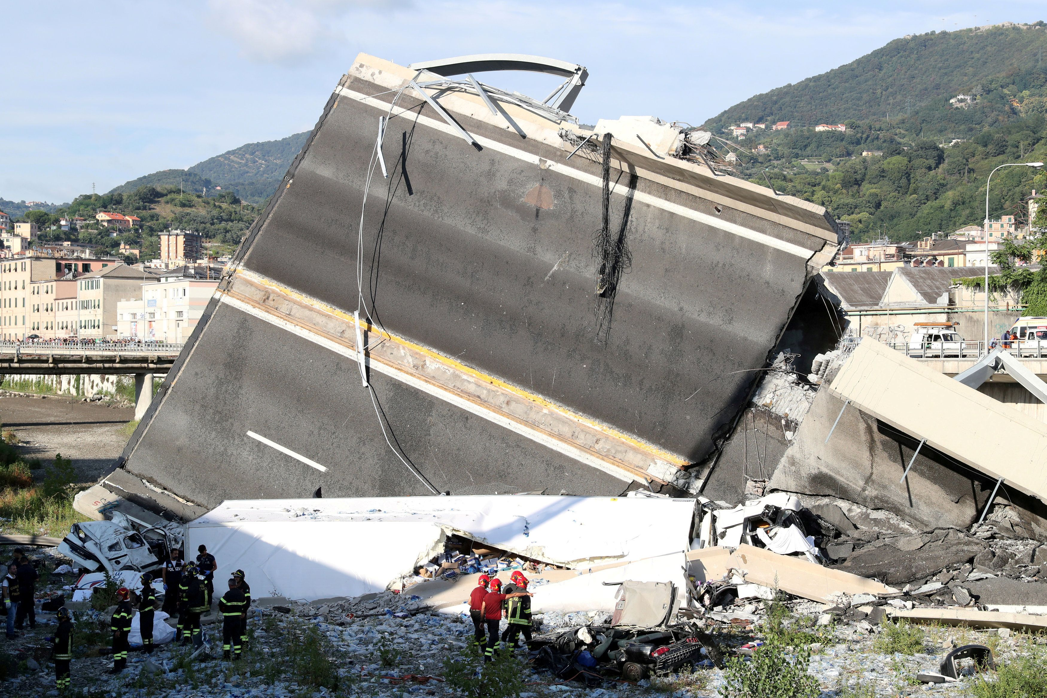 Firefighters and rescue workers stand next to a part of the motorway, at the collapsed Morandi Bridge site in the port city of Genoa, Italy August 14, 2018.  REUTERS/Stefano Rellandini      TPX IMAGES OF THE DAY