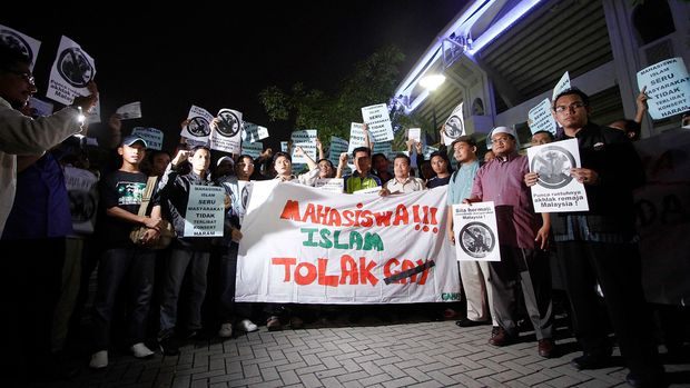 KUALA LUMPUR, MALAYSIA - OCTOBER 14:  Protesters shout slogans during a protest against a concert by American Musician, Adam Lambert outside its venue on October 14, 2010 in Kuala Lumpur, Malaysia. Malaysia's Islamist opposition party is demanding the cancellation of the concert due to the singer's ties to 'gay culture'. Homosexual sex is a criminal offence in Malaysia. The banner reads 'Muslim Students Against Gay'.  (Photo by Syamsul Bahri Muhammad/Getty Images)