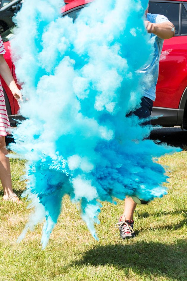 A dad-to-be kicks a soccer ball filled with blue powder to reveal that his baby will be a