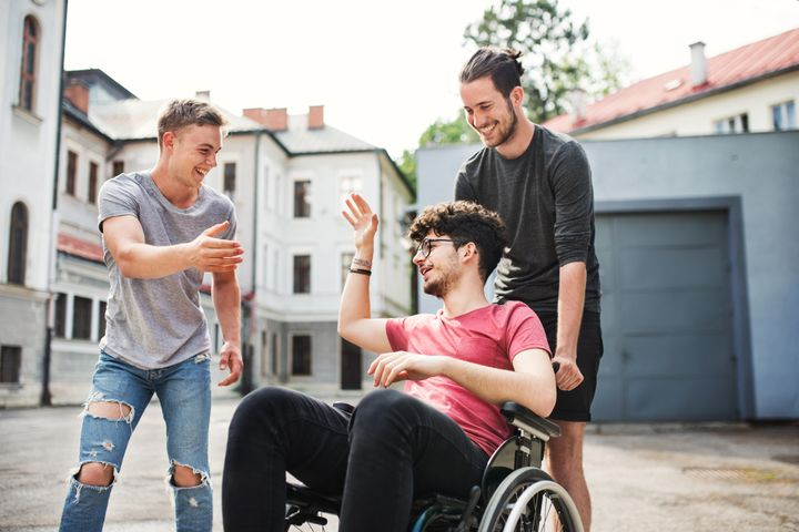 A disabled boy in wheelchair with two teenager friends outside having fun in town.