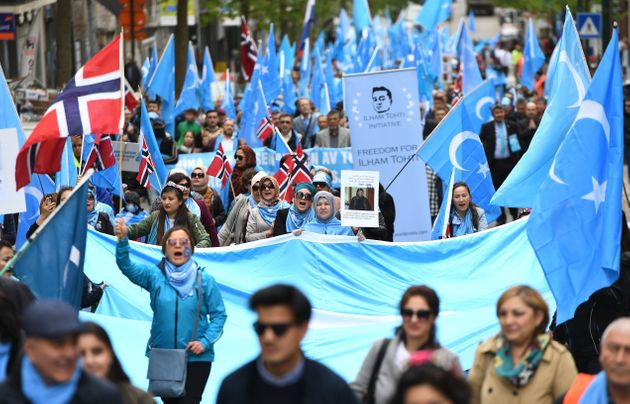 Ethnic Uighurs take part in a protest march near European Union offices in Brussels on April