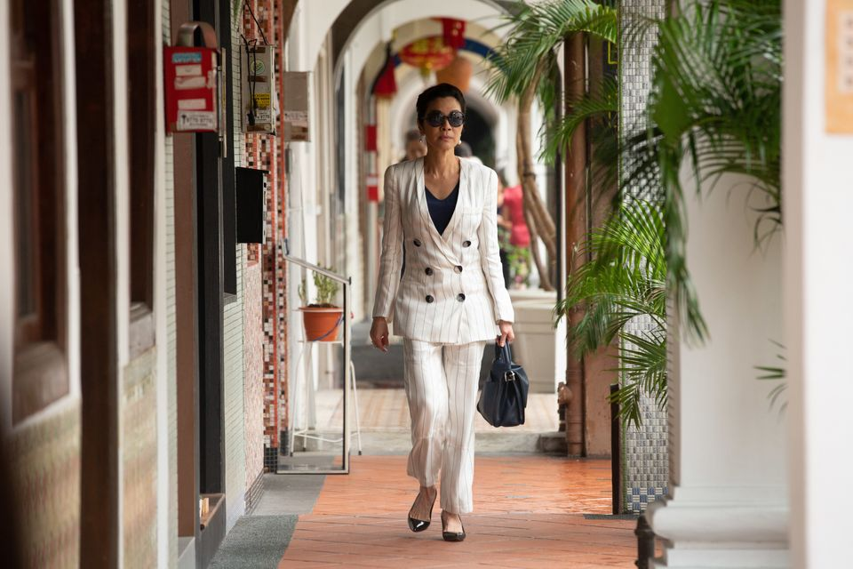 Eleanor Young (Michelle Yeoh) wearing a white crepe Armani suit with navy pinstripes.