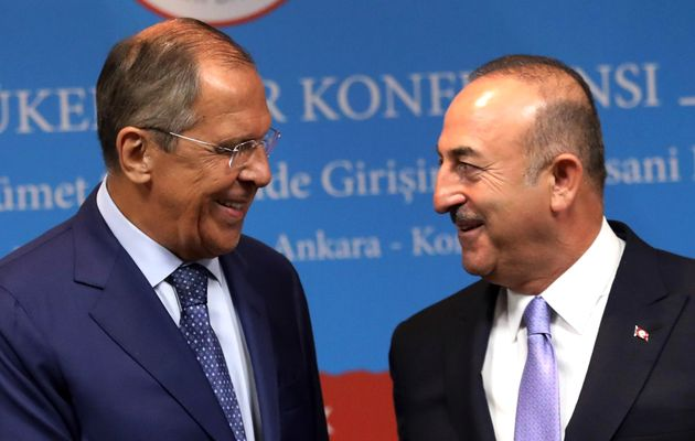 Turkey's Foreign Minister Mevlut Cavusoglu (R) and his Russian counterpart Sergei Lavrov smile during...