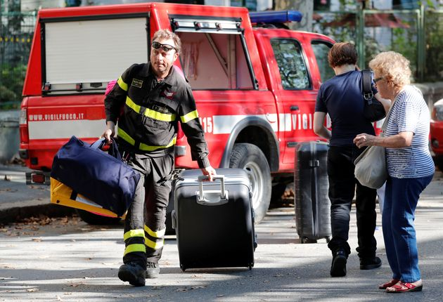 A firefighter carries personal belongings of a woman after she recovered them from her house following...