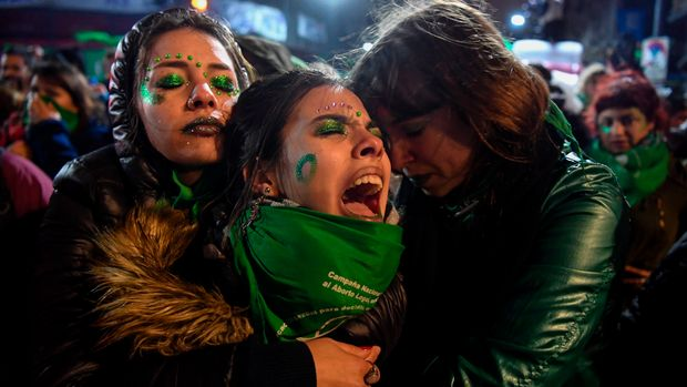 TOPSHOT - Activists in favour of the legalization of abortion comfort each other outside the National Congress in Buenos Aires, on August 9, 2018 after senators rejected the bill to legalize the abortion. - Argentine senators on Thursday voted against legalizing abortion in the homeland of Pope Francis, dashing the hopes of women's rights groups after the bill was approved by Congress's lower house in June. According to an official tally, 38 senators voted against, 31 in favor, while two abstained. (Photo by EITAN ABRAMOVICH / AFP)        (Photo credit should read EITAN ABRAMOVICH/AFP/Getty Images)