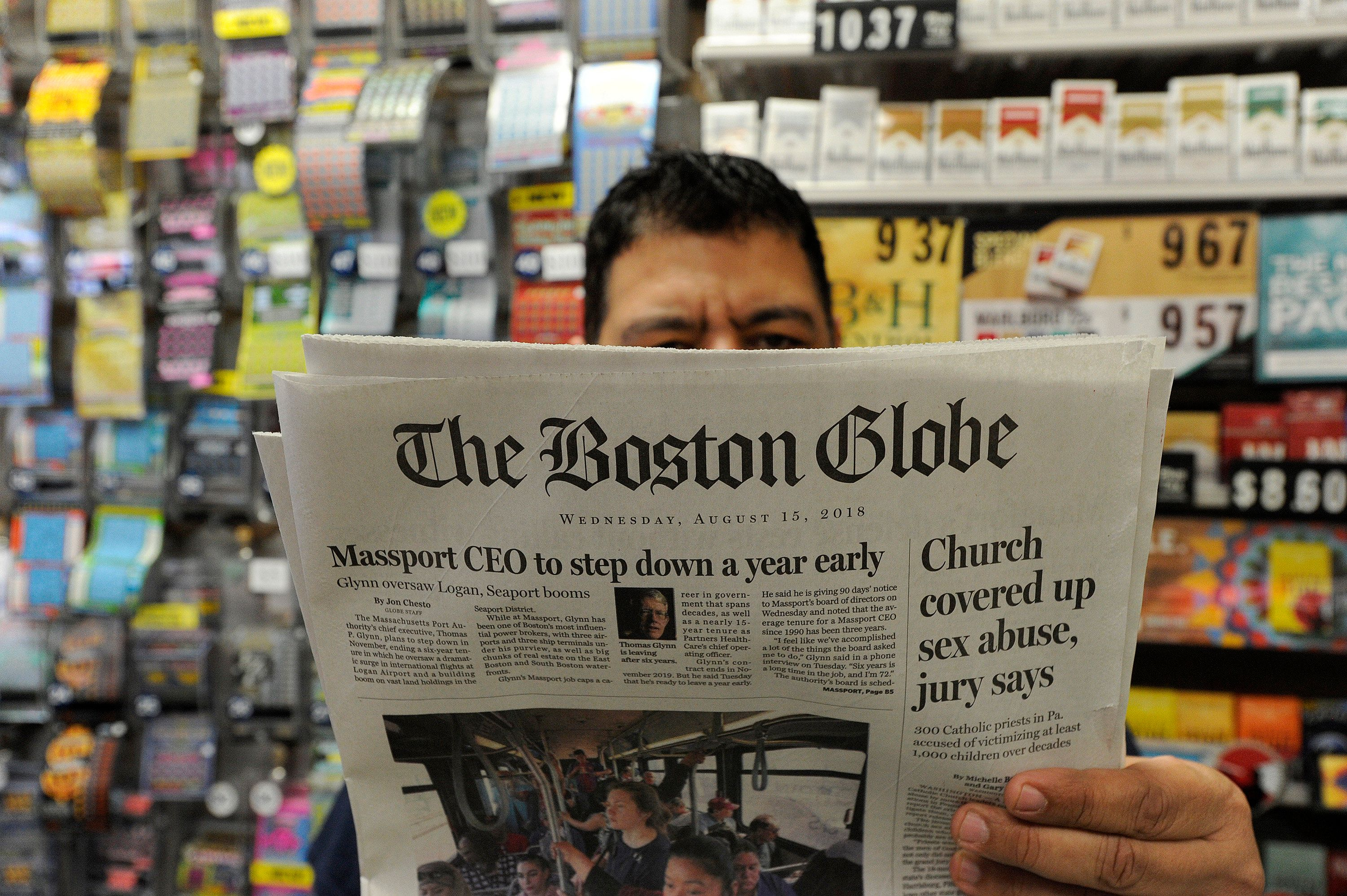 Phillip Minias, 46, owner of Snax Express, reads the Boston Globe, August 15, 2018 in Boston, Massachusetts. - Branded 'enemy of the people' by us President Donald Trump, the US news media is responding with a campaign aimed at countering the president's narrative and highlighting the importance of a free press. More than 200 news organizations are to participate in a coordinated campaign on August 16, 2018, with editorials about the importance of an independent media and a social media hashtag #EnemyOfNone. The move comes in response to a call by the Boston Globe amid a growing sense of unease that Trump's rhetoric is harmful to a free press and may even incite violence against journalists. (Photo by Joseph PREZIOSO / AFP)        (Photo credit should read JOSEPH PREZIOSO/AFP/Getty Images)