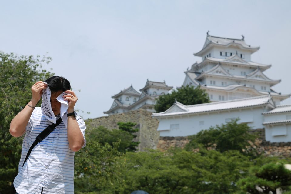 A man attempts to cover his face in Himeji,