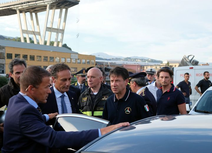 Italian Prime Minister Giuseppe Conte (center) visits the site after a section of the Morandi motorway bridge collapsed earli