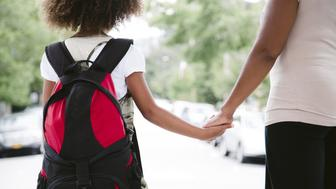 african american mom and daughter hold hands while walking