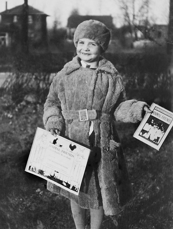 A 5-year-old girl shows off her books after her first day of kindergarten, circa 1929.