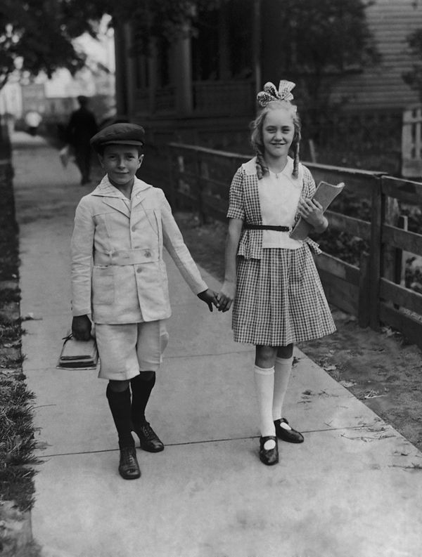 A young boy and girl on the way to school for the start of a new term in the 1920s.