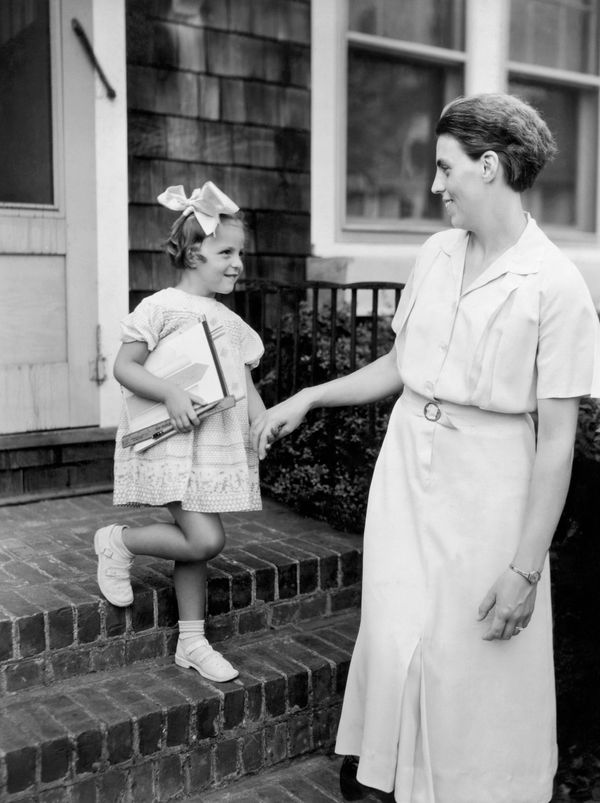 A mother takes her daughter by the hand as they head to school in the late 1920s or early 1930s.