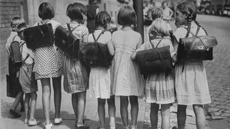 Schoolchildren on their way home from school, with book bags strapped on their backs, after the first day of a new term in Germany circa 1930. (Photo by Keystone View/FPG/Getty Images)