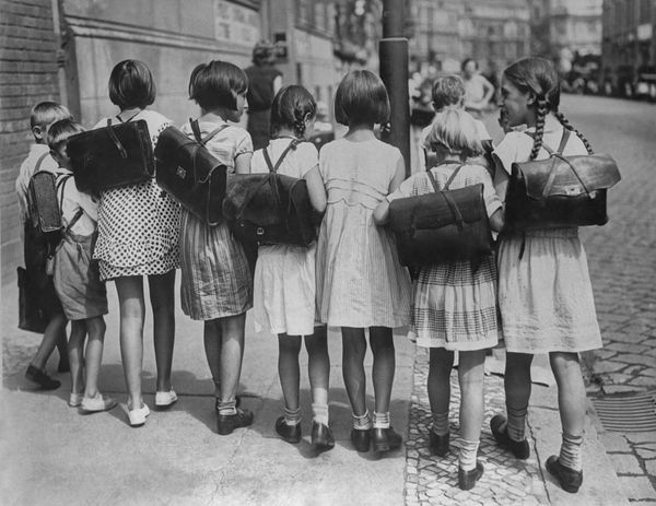 Children on their way home from school, with book bags strapped on their backs, after the first day of classes in Germany, ci