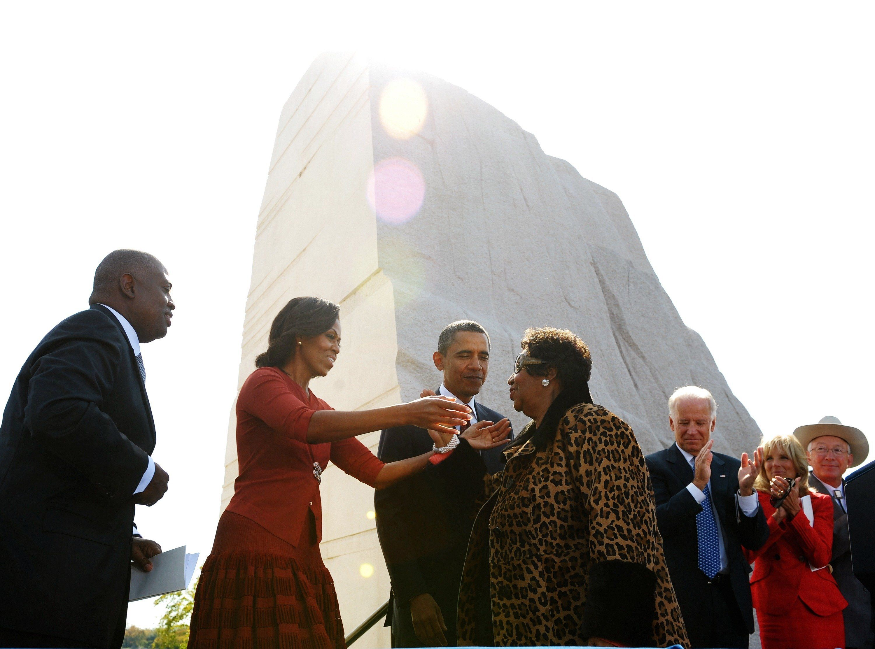 First Lady Michelle Obama reaches out to embrace Aretha Franklin as President and CEO of the Martin Luther King, Jr. National Memorial Project Foundation Harry Johnson (L), US President Barack Obama , Vice President Joe Biden (3rd R), Biden's wife Jill and Interior Secretary Ken Salazar (R) look on after Franklin performed at the dedication of the Martin Luther King Jr. Memorial October 16, 2011 in Washington, DC. AFP PHOTO/Mandel NGAN (Photo credit should read MANDEL NGAN/AFP/Getty Images)