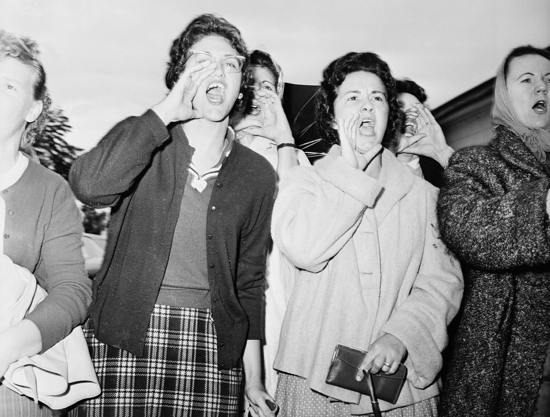 At McDough Elementary in New Orleans, Louisiana, mothers of white students scream as three six-year-old girls enter the school on their fifth day of classes. The New Orleans public school system was ordered shut down all next week for teachers' meetings after the attendance fell off by 1/3 following integration. Outbreaks of violence continued in the city with a reported score of arrests made, attributable to the school integration. November 18, 1960
