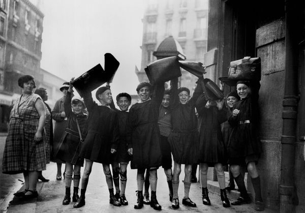 Students in France greet a photographer at the start of a new term by shaking their schoolbags in 1932.
