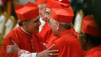 New cardinal Daniel N. DiNardo of the U.S. (L) is greeted after he received the biretta, a four-cornered red hat, from Pope Benedict XVI  during the Consistory ceremony in Saint Peter's Basilica at the Vatican November 24, 2007. Pope Benedict, elevating 23 prelates from around the world to the elite rank of cardinal, made a pressing appeal on Saturday for an end to the war in Iraq and decried the plight of the country's Christian minority.  REUTERS/Tony Gentile (VATICAN)