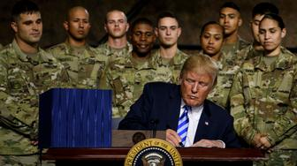 US President Donald Trump signs the John S. McCain National Defense Authorization Act for Fiscal Year 2019 at Fort Drum, New York, on August 13, 2018. (Photo by Brendan Smialowski / AFP)        (Photo credit should read BRENDAN SMIALOWSKI/AFP/Getty Images)