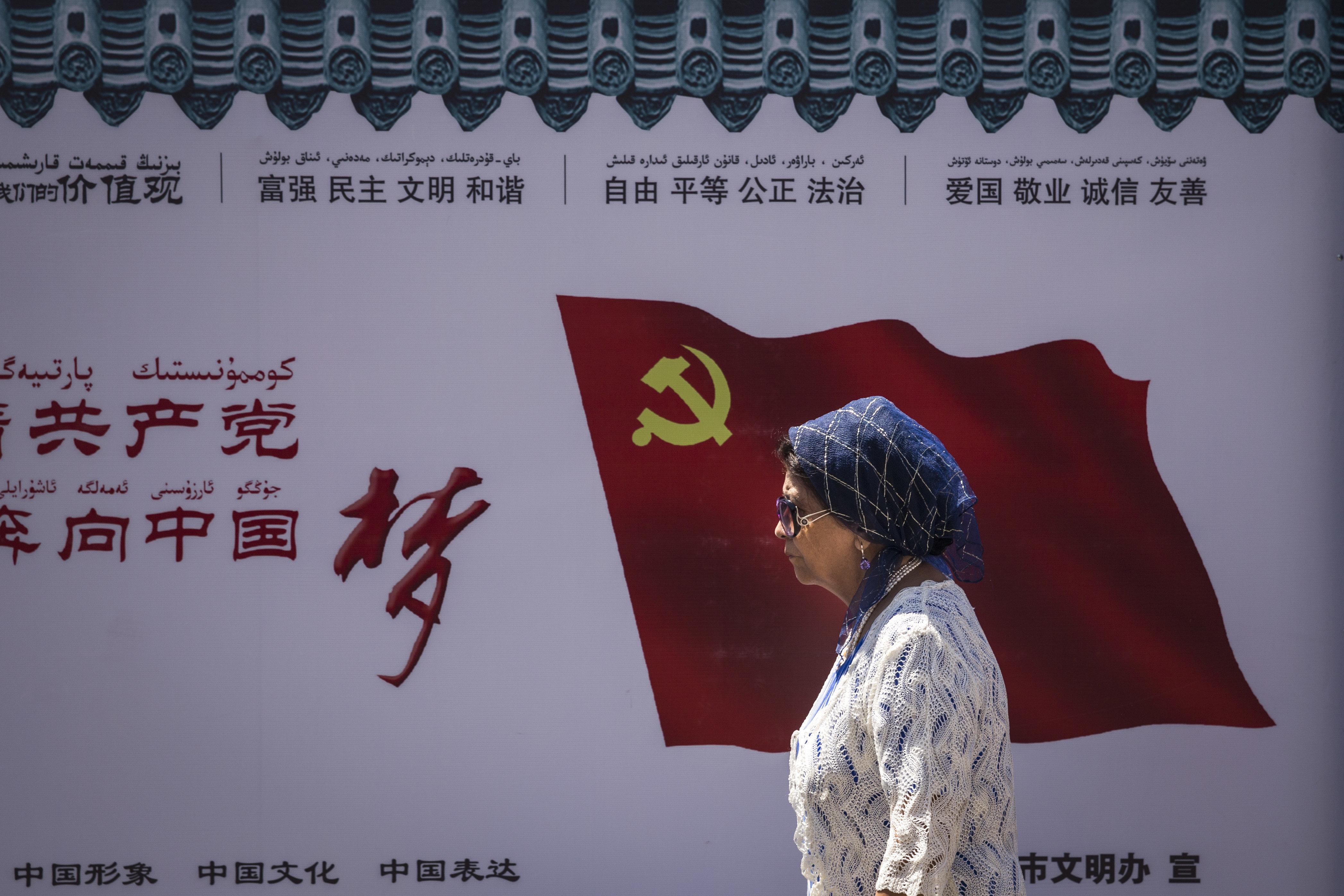 중국 신장위구르자치구 우루무치에서 한 위구르인이 중국 공산당 깃발이 새겨진 벽 앞을 지나고 있다. 2017년