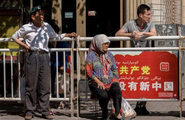 위구르인들이 버스를 기다리는 모습. 배경에 있는 광고판에는 '공산당 없이 새로운 중국은 없을 것'이라는 문구가 적혀있다. 우루무치, 신장위구르자치구, 중국. 2016년