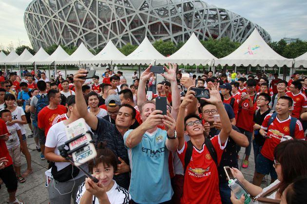 잉글랜드 프리미어리그(EPL) 맨체스터 유나이티드와 맨체스터시티의 유니폼을 입은 중국 팬들이 두 팀의 친선경기 직후 사진을 찍고 있다. 베이징, 중국. 2016년