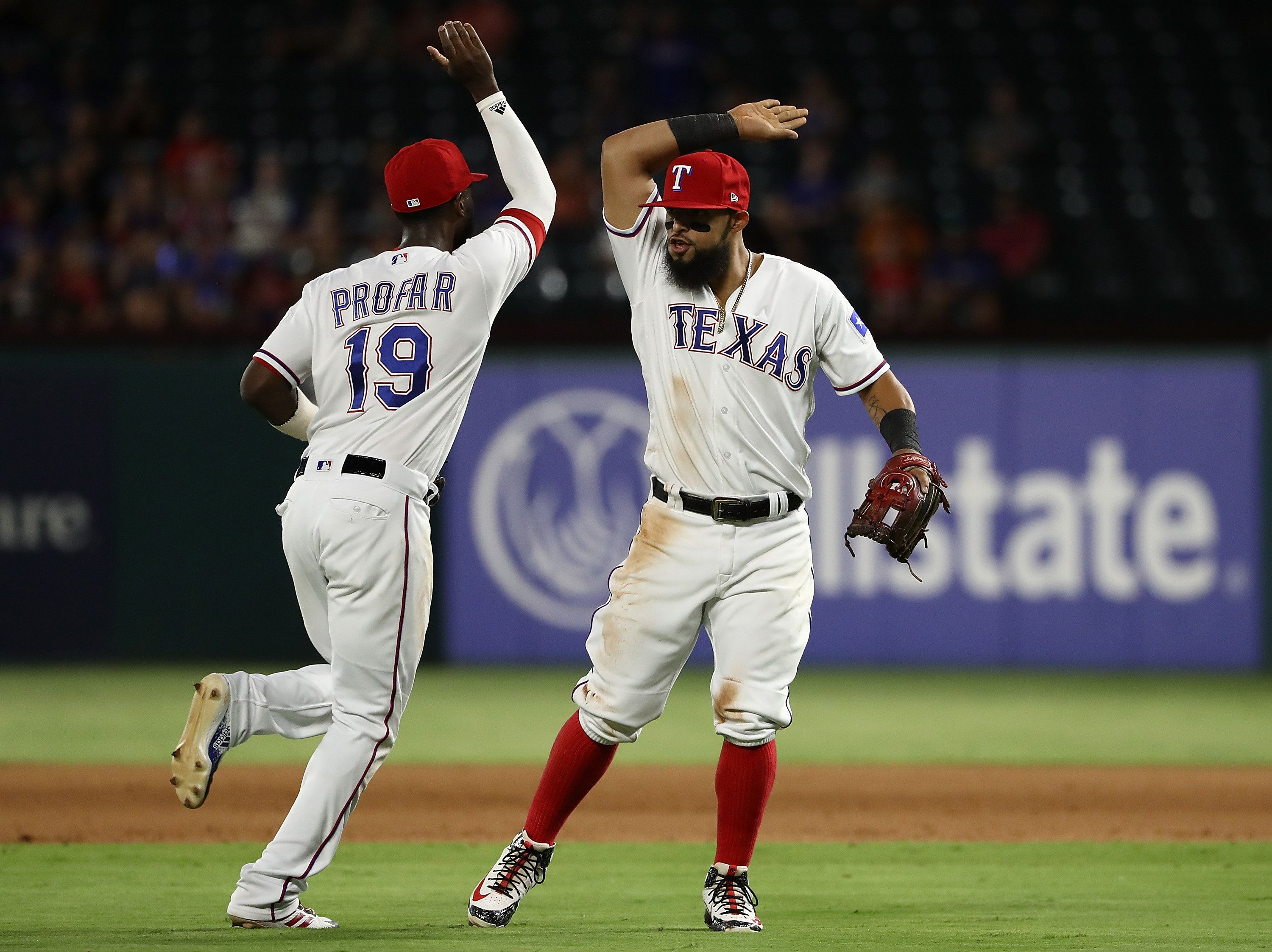 ARLINGTON, TX - AUGUST 16:  (L-R) Jurickson Profar #19 and Rougned Odor #12 of the Texas Rangers celebrate a triple play against the Los Angeles Angels in the fourth inning at Globe Life Park in Arlington on August 16, 2018 in Arlington, Texas.  (Photo by Ronald Martinez/Getty Images)