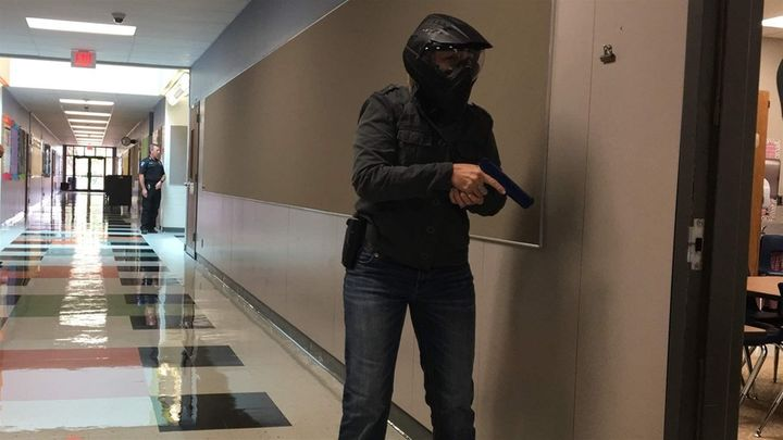 A school marshal trainee, wearing protective headgear, cautiously approaches a classroom in a simulated search for an armed i