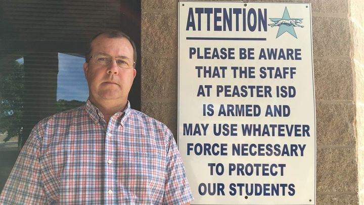 Matt Adams, superintendent of the Peaster Independent School District in Parker County, Texas, stands next to a sign intended