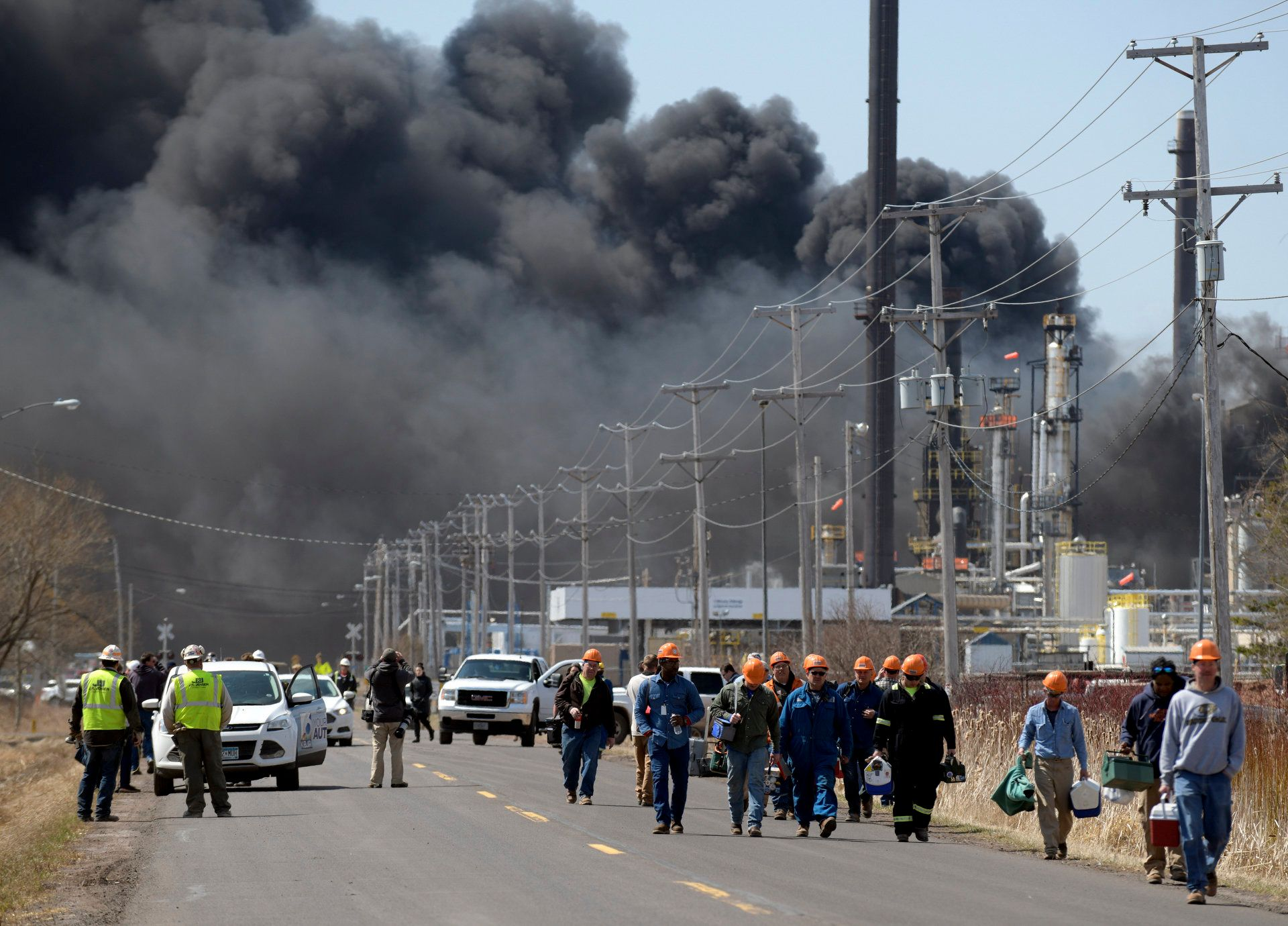 Workers evacuate from an explosion and fire at the Husky Energy oil refinery in Superior, Wisconsin on April 26, 2018. - Several people were injured by an explosion and fire at an oil refinery in the Midwestern US state of Wisconsin on Thursday, sending thick plumes of black smoke into the sky as authorities urged residents in the area to evacuate. (Photo by Jules Ameel / AFP)        (Photo credit should read JULES AMEEL/AFP/Getty Images)