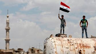 A Syrian youth waves his national flag on top of a bullet-riddled water container on the destroyed Thalateen Street in the Yarmuk Palestinian refugee camp on the southern outskirts of the capital Damascus on May 24, 2018, as civilians return to see their homes after the regime seized the camp and adjacent neighbourhoods of Tadamun and Hajar al-Aswad earlier in the week from the Islamic State (IS) group, putting Damascus fully under its control for the first time since 2012. (Photo by LOUAI BESHARA / AFP)        (Photo credit should read LOUAI BESHARA/AFP/Getty Images)