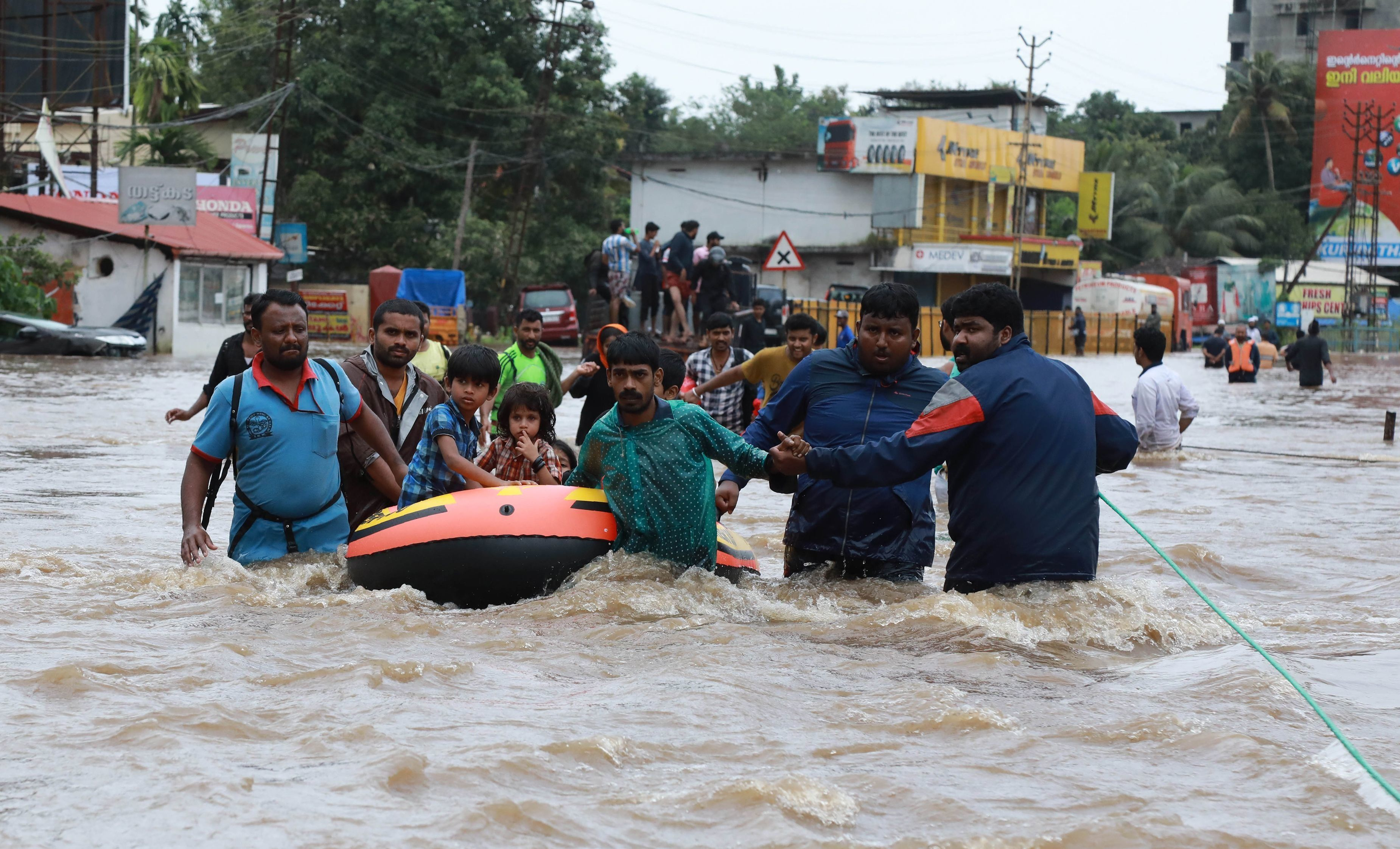 Indian volunteers and rescue personnel evacuate local residents in a boat in a residential area at Aluva in Ernakulam distric