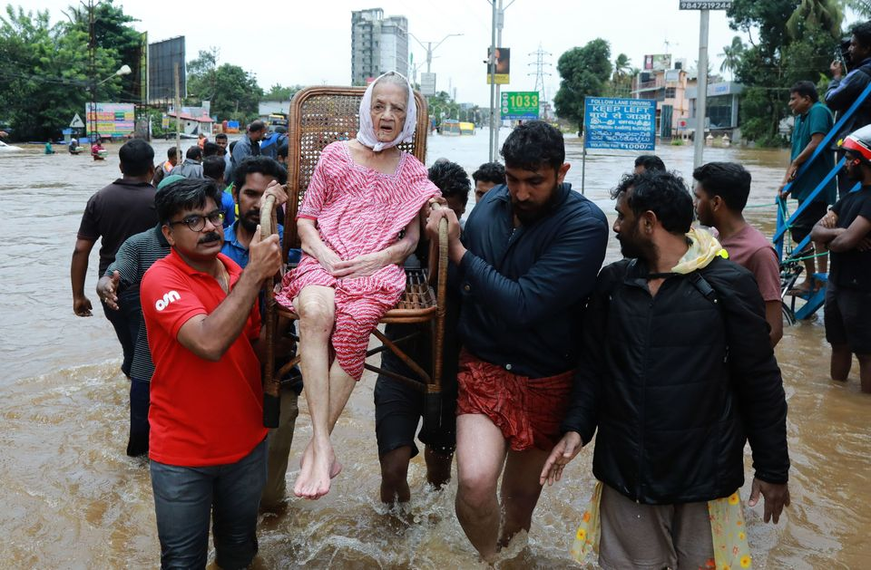 Indian volunteers and rescue personnel evacuate local residents in a residential area in Ernakulam district, in the Indian st