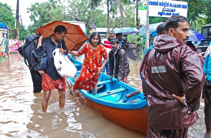 Indian volunteers and rescue personnel evacuate local residents in a boat in a residential area at Kozhikode, in the Indian s