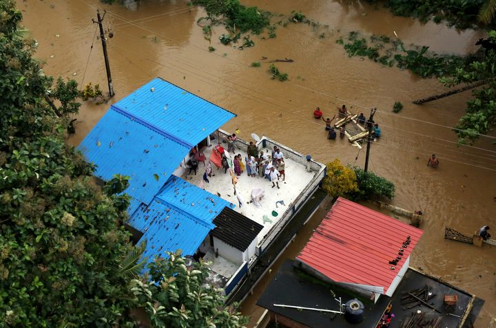 People wait for aid on the roof of their house in a flooded area in Kerala on Aug. 17.