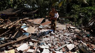 A man holds his child as he walks through the ruins of their house at Kayangan district after earthquake hit on Sunday in North Lombok, Indonesia, August 7, 2018. REUTERS/Beawiharta