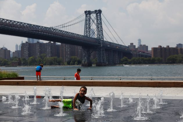 A child cools off from the hot weather at Domino Park in the Williamsburg section of