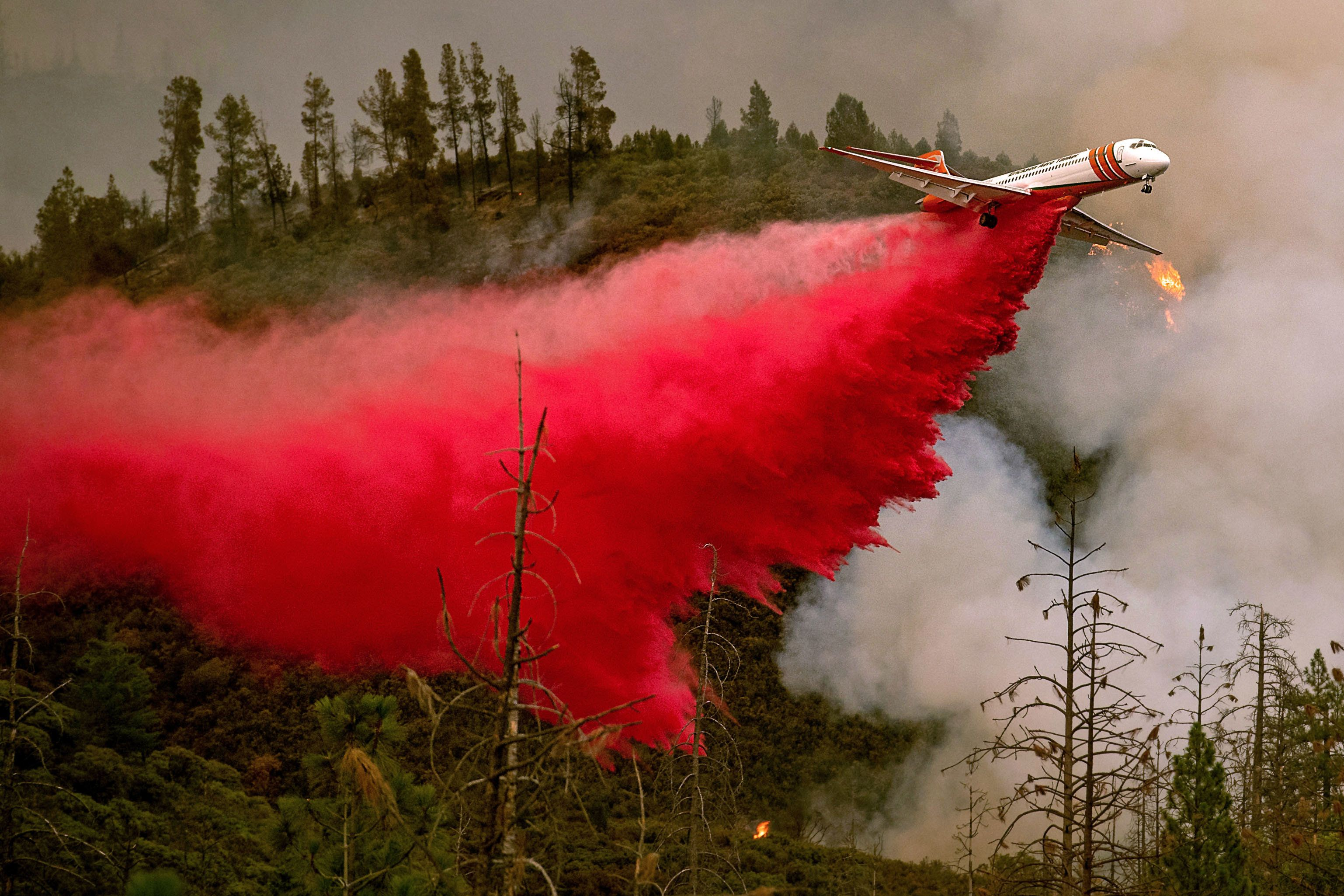 TOPSHOT - An air tanker drops retardant while battling the Ferguson fire in Stanislaus National Forest, near Yosemite National Park, California on July 21, 2018. - A fire that claimed the life of one firefighter and injured two others near California's Yosemite national park has almost doubled in size in three days, authorities said Friday. The US Department of Agriculture (USDA) said the so-called Ferguson fire had spread to an area of 22,892 acres (92.6 square kilometers), and is so far only 7 percent contained. (Photo by NOAH BERGER / AFP)        (Photo credit should read NOAH BERGER/AFP/Getty Images)