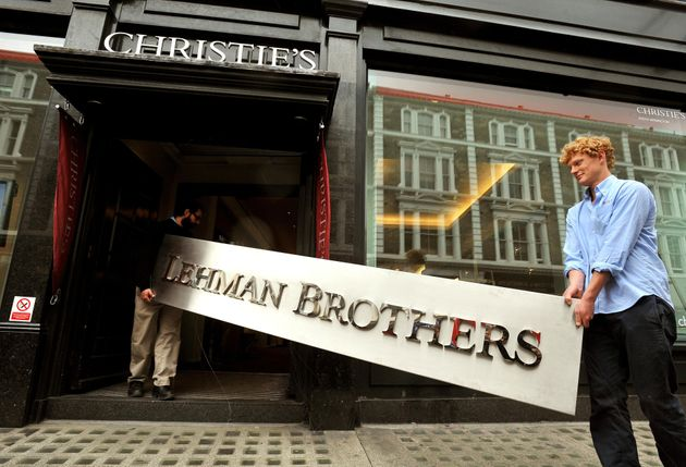 Christie's employees walk into the auction rooms with the main sign from the Lehman Brothers London office...