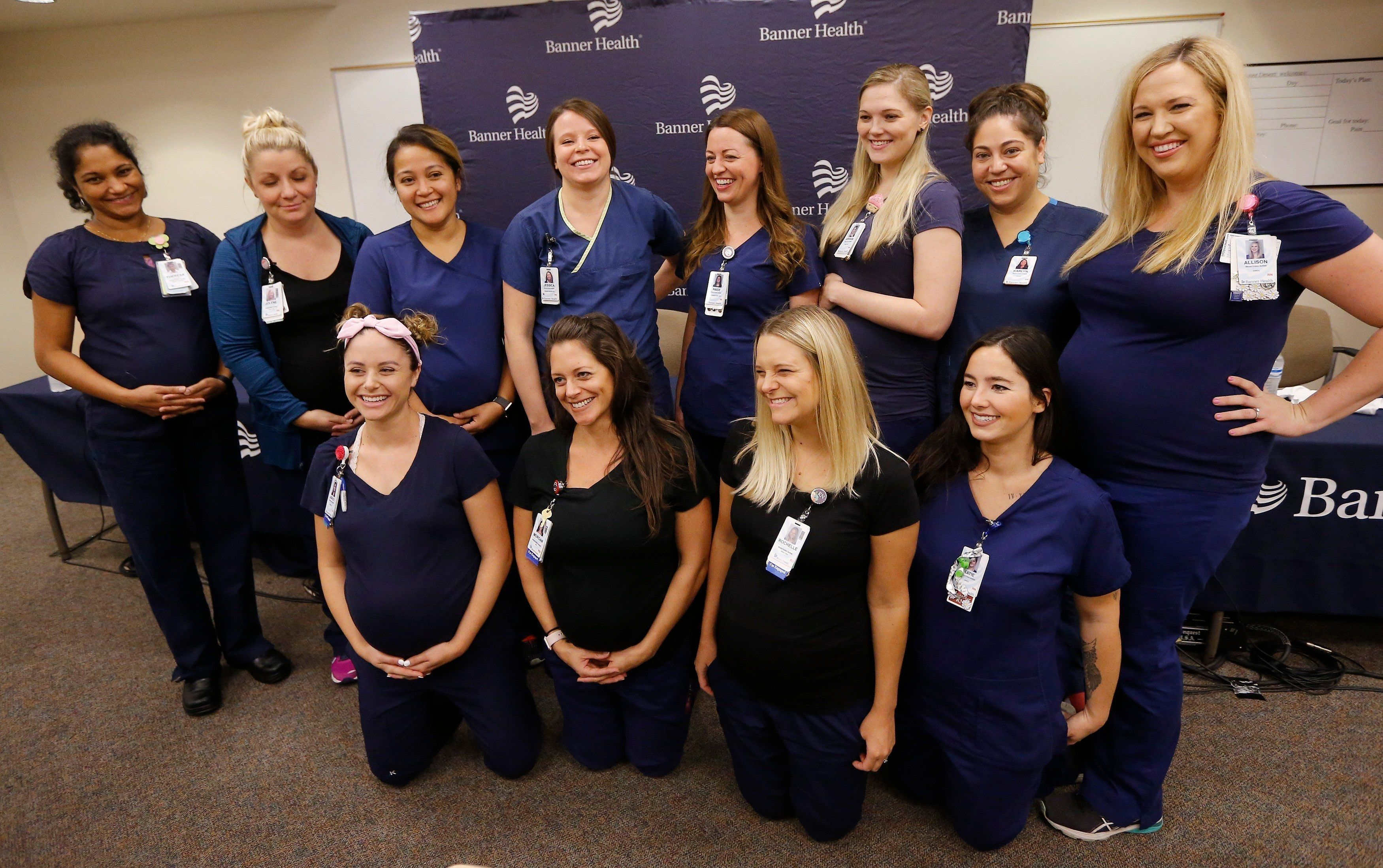 Twelve of the 16 pregnant nurses pose for a photograph after a press conference on Aug. 17, 2018.
