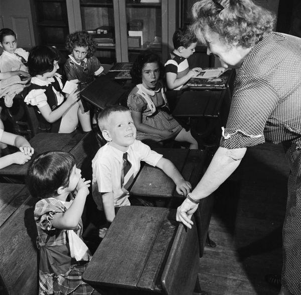 Children getting to know their new teacher, circa 1950.